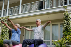 Senior couple exercising on fitness ball. In lawn Royalty Free Stock Photos