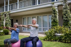 Senior couple exercising on fitness ball. In lawn Royalty Free Stock Images