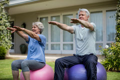 Senior couple exercising on fitness ball. In lawn Stock Photos