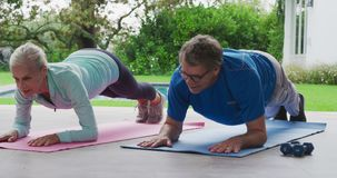 Senior couple exercising in a garden