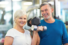 Senior couple exercising in gym Stock Photos
