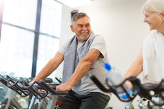 Senior couple exercising in gym Stock Photo