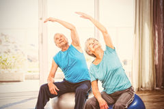Senior couple exercising at home. Senior couple with arms raised while performing exercise at home Royalty Free Stock Photo