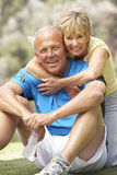 Senior Couple Exercising In Park Stock Photography