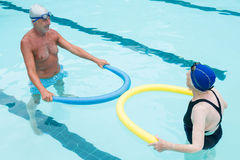 Senior couple exercising with pool noodle. In swimming pool Stock Images