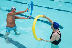 Senior couple exercising with pool noodle. In swimming pool Royalty Free Stock Photo