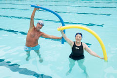 Senior couple exercising with pool noodle in swimming pool. Portrait of senior couple exercising with pool noodle in swimming pool Royalty Free Stock Photo