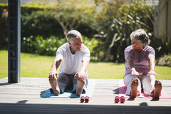 Senior couple exercising together on mat at porch Stock Photography