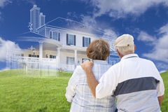 Senior Couple Faces Ghosted House Drawing, Green Grass Hill Behi. Senior Couple Faces Ghosted House Drawing, Partial Photo and Rolling Green Hills Behind Royalty Free Stock Photography