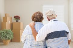 Senior Couple Facing Empty Room with Packed Moving Boxes and Pot. Ted Plants Stock Images