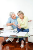 Senior couple fighting over money. Senior couple with paperwork fighting over money at home Royalty Free Stock Photo