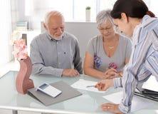Senior couple at financial advisor Stock Photo