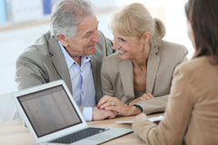 Senior couple with financial advisor. Senior couple meeting financial adviser in office Stock Photos