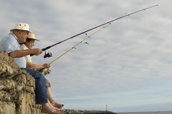 Senior Couple Fishing Against Cloudy Sky Stock Image