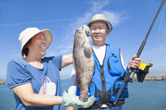Senior couple fishing and showing big grouper Stock Images