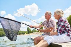 Senior couple with fishing tackle and landing net at the lake. Senior couple with fishing tackle and landing net while fishing together in the summer by the lake royalty free stock images