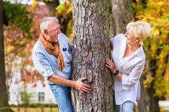 Senior couple flirting playing around tree in park Stock Images