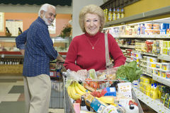 Senior Couple Food Shopping In Supermarket. Smiling senior couple food shopping in supermarket Stock Images