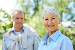 Senior Couple in Forest. Portrait of contemporary senior woman smiling at camera with loving husband in background, copy space royalty free stock photo