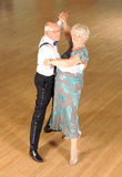 Senior Couple at Formal Dance. A retired, senior couple performing a formal ballroom dance hold on a wooden floor Stock Photo