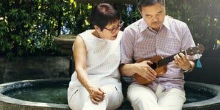 Senior Couple Fountain Ukelele Instrument Concept Royalty Free Stock Image