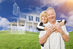 Senior Couple In Front of Ghosted House Drawing on Grass. Senior Couple In Front of Ghosted House Drawing, Partial Photo and Rolling Green Hills Behind Royalty Free Stock Images