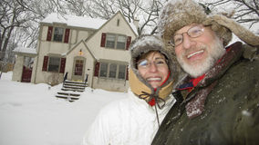 Senior couple in front of house. Happy senior couple standing in front of house in winter Royalty Free Stock Photos