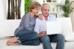 Senior couple in front of laptop. Senior couple sitting with laptop computer Stock Photo