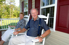Senior couple on front porch. A happy senior couple sitting on the front porch of a home in rocking chairs Stock Image