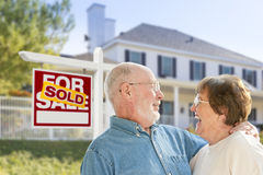 Senior Couple in Front of Sold Real Estate Sign, House. Happy Affectionate Senior Couple Hugging in Front of Sold Real Estate Sign and House royalty free stock images
