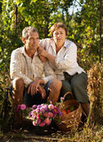 Senior couple in garden. Portrait of senior couple in garden with flowers and basket Royalty Free Stock Image
