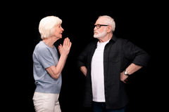 Senior couple gesturing. Side view of senior couple standing and gesturing isolated on black Stock Photo