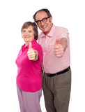 Senior couple gesturing thumbs up. Towards camera, isolated Royalty Free Stock Images
