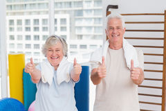 Senior couple gesturing thumbs up in gym. Portrait of happy senior couple gesturing thumbs up in gym Stock Images