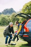 Senior Couple Getting Ready to Hike. Senior couple have arrived to a national park in their car. The women is sitting on the edge of the car boot and the men is Stock Photo