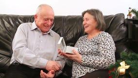 Senior couple with gift near Christmas tree stock footage