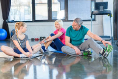 Senior couple and girl sitting on yoga mats in fitness class Royalty Free Stock Images