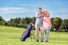Senior couple giving thumbs up on a golf course. Attractive senior couple giving thumbs up on a golf course. Happiness and satisfaction Stock Photography