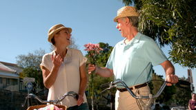Senior couple going on a bike ride in the city with man bringing flowers stock footage