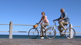 Senior couple going on a bike ride in the city on the pier stock footage