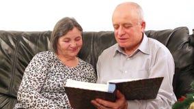 Senior couple going through photo album on Christmas stock video