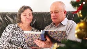 Senior couple going through photo album on Christmas stock video footage