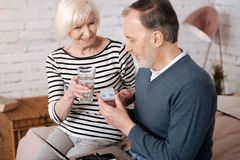 Senior couple going to take pills. It will help. Smiling senior lady is offering water glass to her husband going to take pills Stock Photo