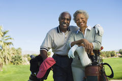 Senior Couple In Golf Course. Portrait of happy senior couple in golf course smiling Stock Photography