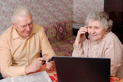 Senior couple gossip about something by phone. At home Stock Photos