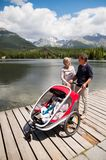 Senior couple with grandchildren in jogging stroller. Senior couple and grandchildren in jogging stroller, summer day. High mountains in the background Stock Photography