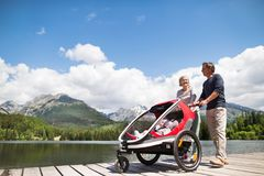 Senior couple with grandchildren in jogging stroller. Senior couple and grandchildren in jogging stroller, summer day. High mountains in the background Stock Image
