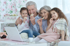 Senior couple with grandchildren  and laptop Stock Photos