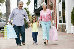 Senior Couple With Granddaughter Carrying Shopping Bags Royalty Free Stock Images