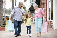 Senior Couple With Granddaughter Carrying Shopping Bags Stock Photo
